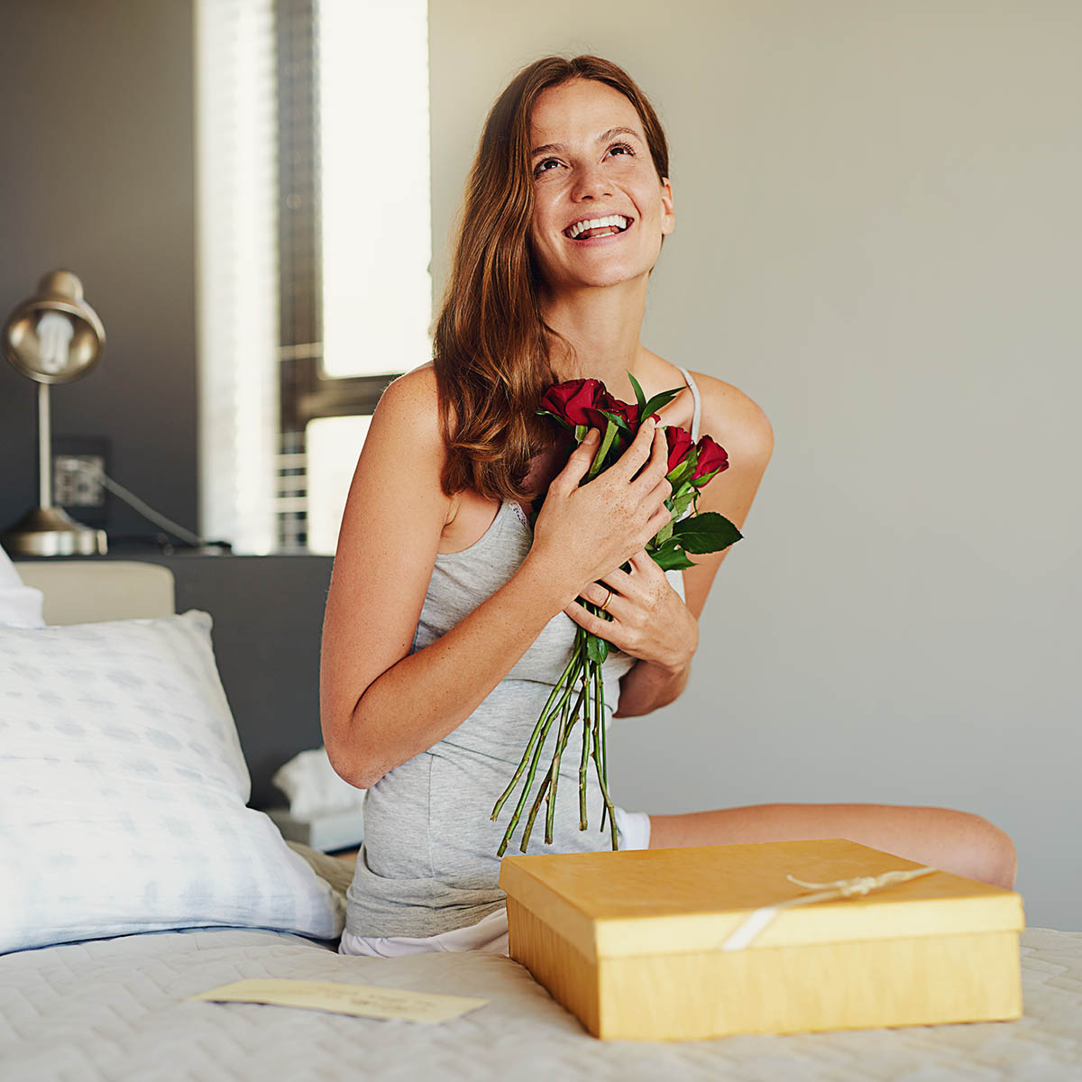 Shot of a woman opening a gift at home
